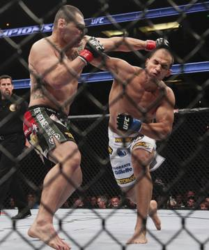 Junior dos Santos, right, of Brazil, fights Cain Velasquez in the UFC mixed martial arts heavyweight title bout Saturday, Nov. 12, 2011, in Anaheim, Calif. Dos Santos won by knockout in the first round.