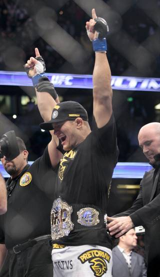 Junior dos Santos, of Brazil, gets the title belt after defeating Cain Velasquez in the UFC mixed martial arts heavyweight title bout, Saturday, Nov. 12, 2011, in Anaheim, Calif.