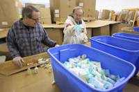 Mike Brennan, left, and James Benson sort hotel shampoo, lotion and conditioner bottles at Clean the World Wednesday, Nov. 16, 2011.