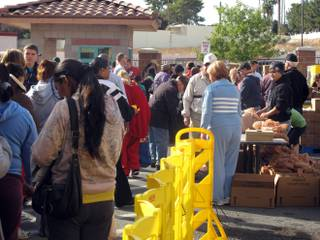 Thousands of men and women wait in line for turkeys, canned foods and pies at the Catholic Charities turkey box giveaway Saturday, Nov. 19, 2011.
