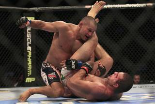 Dan Henderson, top, punches Mauricio Rua during the fourth round of a UFC 139 Mixed Martial Arts light heavyweight bout in San Jose, Calif., Saturday, Nov. 19, 2011. Henderson won by unanimous decision.