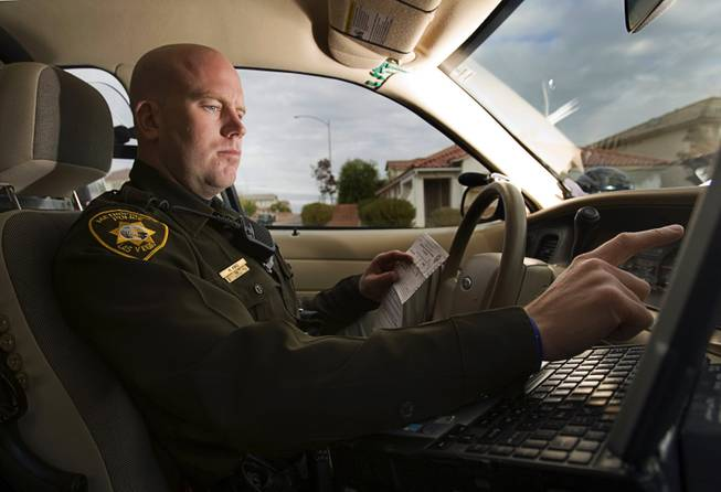 Metro Police Officer Harrison King uses his computer during a vehicle stop Monday, Nov. 21, 2011. When not performing other duties, Officer King keeps an eye open for students who are skipping school as part of Metro's TARDY (Taking Action Regarding Delinquent Youth) program.