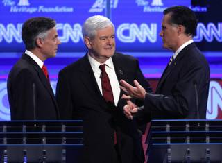 Republican presidential candidates former Utah Gov. Jon Huntsman and former House Speaker Newt Gingrich talk with former Massachusetts Gov. Mitt Romney at a Republican presidential debate in Washington, Tuesday, Nov. 22, 2011.