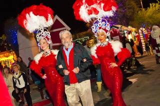 Ed Guthrie, the Executive Director for Opportunity Village, walks escorted by 2 showgirls to the Magical Forrest, Friday Nov. 25, 2011.