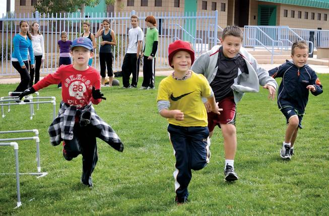 A group of boys runs to the next station of an obstacle course during home school boot camp at Centennial Hills Park.
