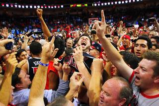 UNLV forward Carlos Lopez celebrates the Rebels' upset of UNC with a court full of fans at the Las Vegas Invitational championship game Saturday, Nov. 26, 2011, at the Orleans Arena. UNLV beat the No. 1-ranked Tar Heels 90-80.