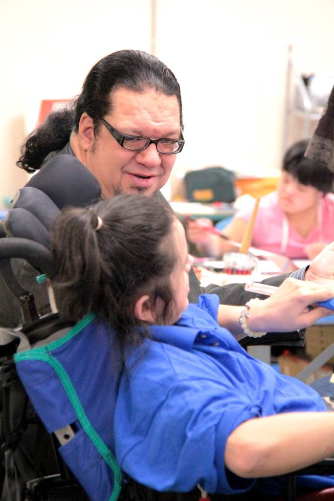 "After advancing to another round on ""Celebrity Apprentice,"" Penn Jillette visits Opportunity Village to deliver a check worth $40,000 earned from his wins on the show."