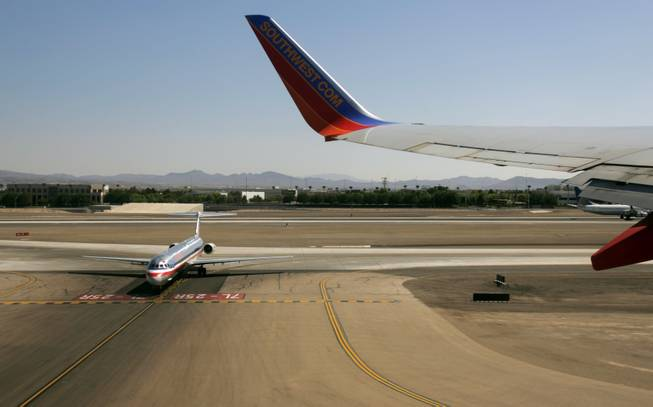 An American Airlines jet waits to taxi as a Southwest Airlines jet takes off from McCarran International Airport in this 2009 file photo.