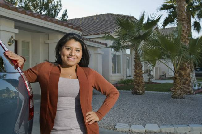 Allison Cordova poses outside of her home Monday, Dec. 5, 2011. Cordova, who closed on the home in October, said homeownership seemed to make sense when mortgage payments rivaled rental rates.