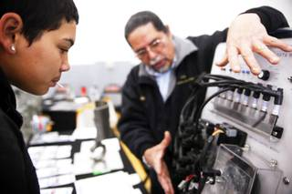 Junior Dominic Cardenas, left, checks out a demonstration by instructor Edgardo Rapala of the College of Southern Nevada Transportation Technologies Program during a job fair at Chaparral High School in Las Vegas Tuesday, December 6, 2011.