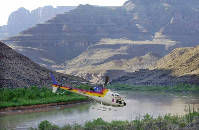 A Eurocopter AS350, similar to the Sundance Helicopters aircraft that crashed Wednesday near Lake Mead, is shown taking off in front of a section of the Grand Canyon in this 2001 file photo. The helicopter pictured is from a different tour operator.