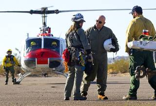 Clark County Coroner Michael Murphy, second from right, talks with Metro Police Search and Rescue officers after viewing a helicopter crash site near Lake Mead Thursday, December 8, 2011. Five people were killed when a tour helicopter crashed near the lake Wednesday. .