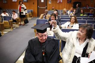 Michael Zone, 90, a Desert Rose High School graduate,gets some help with his tassel from his wife Mary Zone before accepting his diploma during the Clark County School District board meeting at the Greer Education Center in Las Vegas Thursday, December 8, 2011.