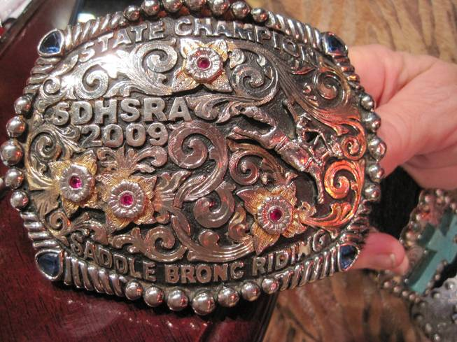 Sindi Jandreau shows the buckle of her son, a 2009 high school rodeo champion from South Dakota.