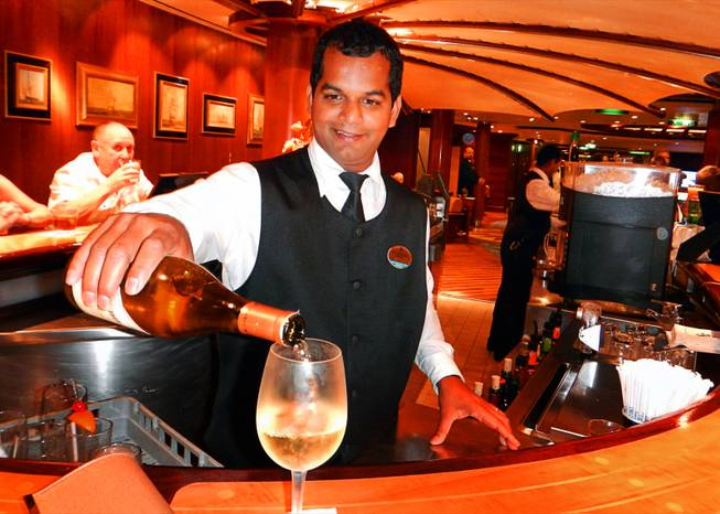 In Dubai, United Arab Emirates, a bartender on the Brilliance of the Seas cruise ship pours a glass of wine while in port. December  2011.