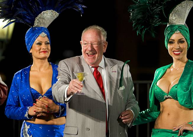 Former Las Vegas Mayor Oscar Goodman takes the stage with a martini and showgirls before an event Thursday, Oct. 13, 2011. Goodman now acts as the city's ambassador.