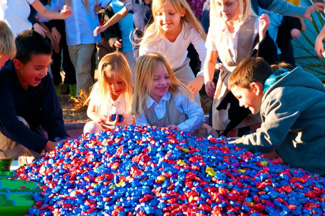 Students at DJ's Christian Academy rush to fill their pockets from a 15,000-plus pile of Dove chocolates, Wednesday Dec. 14, 2011. In12Days, a charity organization, surprised the students with a very special chocolate delivery.