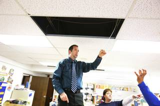 Principal Tim Adams of Rex Bell Elementary School checks out a roof leak on school grounds in Las Vegas Wednesday, Dec. 14, 2011.