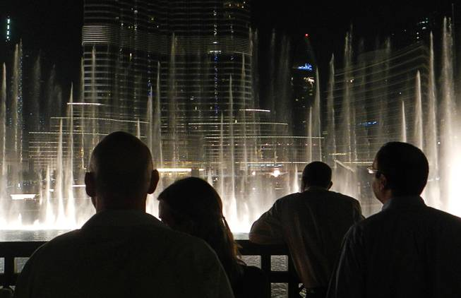 In Dubai, United Arab Emirates, tourists and locals enjoy a display of the Dubai Fountain at the Burj Khalifa complex.  December  2011.
