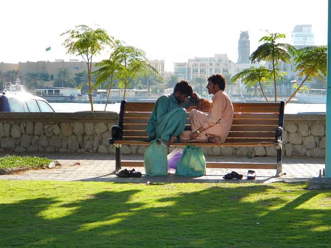 In Dubai, United Arab Emirates, two labor workers chat during their lunch break near Deira Creek. December  2011.