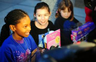 Kynedi Harris, 10, talks with the media as Jolie Leach, 11, looks on after the private Justin Bieber concert at Whitney Elementary School on Friday, Dec. 16, 2011. Bieber donated $100,000 to the east Las Vegas school, which serves many homeless and low-income students.