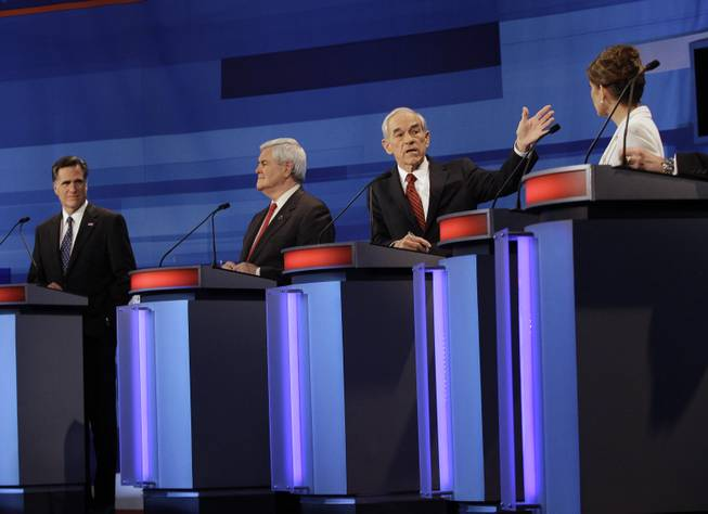 Republican presidential candidates from left, former Massachusetts Gov. Mitt Romney, former House Speaker Newt Gingrich, Rep. Ron Paul, R-Texas, and Rep. Michele Bachmann, R-Minn., participate in a Republican presidential debate in Sioux City, Iowa, Thursday, Dec. 15, 2011.
