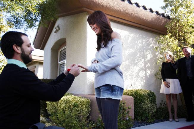 Evan Faircloth proposes to his girlfriend Amy Balogh in front of her family home in Henderson on Saturday, Dec. 17, 2011.
