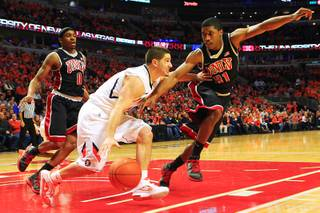 UNLV guard Justin Hawkins defends Illinois guard Sam Maniscalco during their game Saturday, Dec. 17, 2011 at the United Center in Chicago. The Rebels beat the 19th-ranked Illini 64-48.