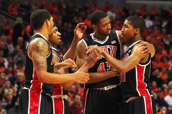 UNLV guard Justin Hawkins is congratulated by teammates, from left, Anthony Marshall, Oscar Bellfield and Mike Moser after drawing a foul against Illinois during their game Saturday, Dec. 17, 2011 at the United Center in Chicago. The Rebels beat the 19th-ranked Illini 64-48.