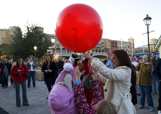 "Amanda Gibbs, right, development director of Boys Town catches a balloon during the 7th day of the 12 days of Christmas at the Village at Lake Las Vegas Monday, Dec.18, 2011. A ""swan"" attached to each balloon holds play money that represents a charitable donation. The donations went to DJ's Community Christian Academy, St. Judes and Boys Town. In12Days is a volunteer-based project aiming to bring the 12 days of Christmas to unsuspecting people in the Las Vegas Valley."