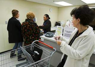 A donor, center, steps up to the counter at the layaway department of a Kmart store on Eastern Avenue in Henderson on Dec. 20, 2011 to pay on the account of Jennifer Wells, left, and another customer. Layaway customer Barbara Poole looks on at right. Anonymous donors, dubbed