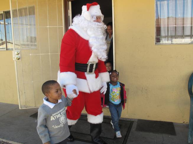 Santa surprises 3-year-old Tristina and 4-year-old Trenton Wednesday afternoon with presents from Operation Fire H.E.A.T. Their North Las Vegas home and Christmas presents were destroyed in an accidental fire Dec. 15