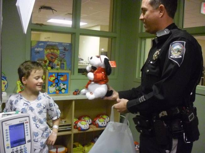 Trooper Bobby Borchardt hands Colin Clifford, 7, toys during NHP's visit to Sunrise Children's Hospital Thursday afternoon.