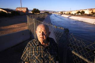 North Las Vegas homeowner Rex Austin stands near near Sloan Channel, which is located close to his home, on Monday, Dec. 26, 2011. Austin is complaining that the North Las Vegas wastewater treatment plant is releasing water into the channel that is causing growth in fungus gnats and chronomid midges around his home. Clark County and the plant are in a legal battle over the issue.
