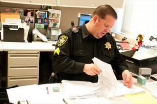 Sgt. Patrick Geary of the Las Vegas Township Constable's Office gets paperwork prepared before heading out in to the city to perform his duties, Wednesday, Dec. 28, 2011.