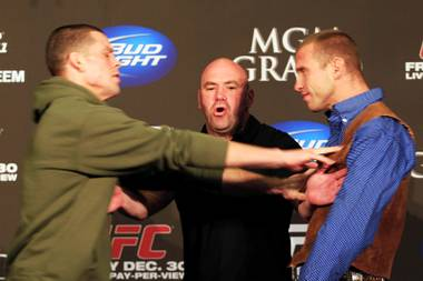 UFC President Dana White separates Nate Diaz, left, and Donald Cerrone after Diaz shoved Cerrone during a news conference Wednesday, Dec. 28, 2011 in advance of UFC 141 on Friday.