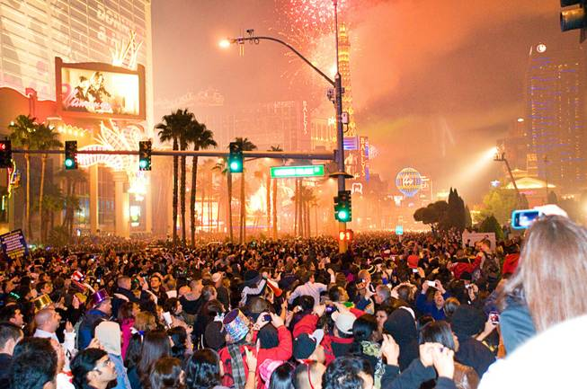 Crowds watch and react to the fireworks display above the Strip on New Year's Eve, Saturday, Dec. 31, 2011.