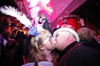 Troy and Tracy Neujahr, of Nebraska, kiss during TributePalooza at the Fremont Street Experience in downtown Las Vegas on New Year's Eve just after midnight on Sunday, Jan. 1, 2012.