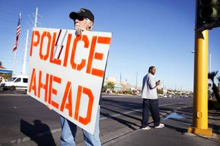 Rich Brown of Sacramento, Calif., and part of a group called Bikers of Lesser Tolerance, a Second Amendment advocacy group, warns motorists using their cellphones of Las Vegas Metro Police's Traffic Bureau patrol near Flamingo Road and Maryland Parkway on Friday, Jan. 6, 2012.