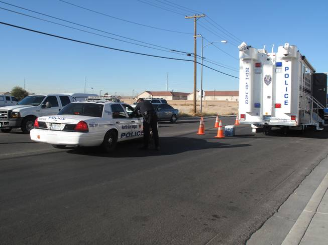 North Las Vegas Police gather in the 2100 block of Lawry Avenue, near the site of an armed standoff Friday, Jan. 6, 2012, between police and two men spotted fleeing from a pawn shop where an armed robbery had been reported.