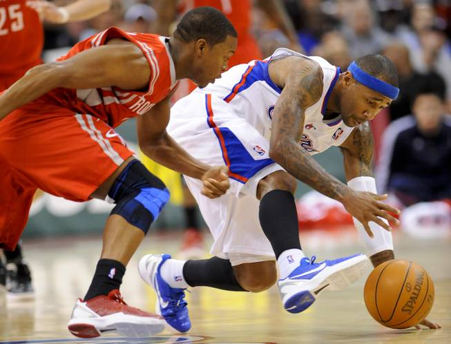 Houston Rockets guard Kyle Lowry, left, and Los Angeles Clippers guard Mo Williams, right, scramble for a loose ball in the first half of a NBA basketball game, Wednesday, Jan. 4, 2012, in Los Angeles.