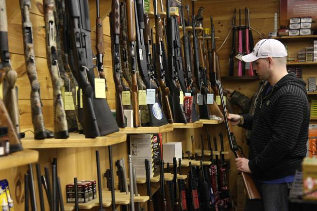 Customers at the State Line Gun Store in Mason, N.H., on Jan. 6, 2012, inspect rifles. Gun stores in New Hampshire, where residents are protective of their Second Amendment rights, are like casinos in Nevada: a mecca that draws customers from neighboring states.