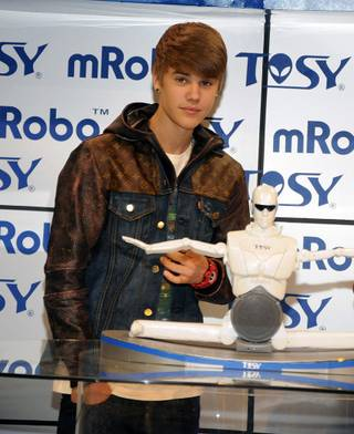 Justin Bieber helps TOSY unveil its entertainment robot at the Consumer Electronics Show at the Las Vegas Convention Center on Jan. 11, 2012.