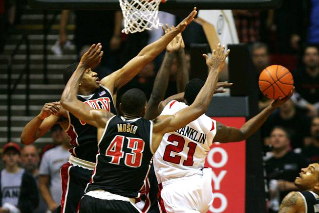 UNLV's Oscar Bellfield, left, Mike Moser and Brice Massamba (not seen) guard San Diego State guard Jamaal Franklin as he takes a last second shot to win the game Saturday, Jan. 14, 2012 at Viejas Arena in San Diego. San Diego State won the Mountain West Conference opener 69-67.