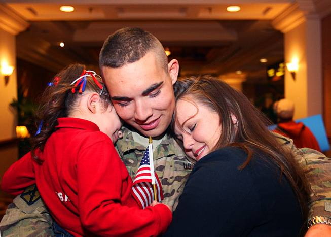 Army National Guard Spc. Michael Sena hugs his daughter Tayler Marie, 3, and his wife Nicole before a welcome home ceremony for the 422nd Expeditionary Signal Battalion at the Mandalay Bay Sunday, January 15, 2012. The Army National Guard soldiers entered field service on January 7, 2011 and have been serving in Afghanistan since March 28, 2011.