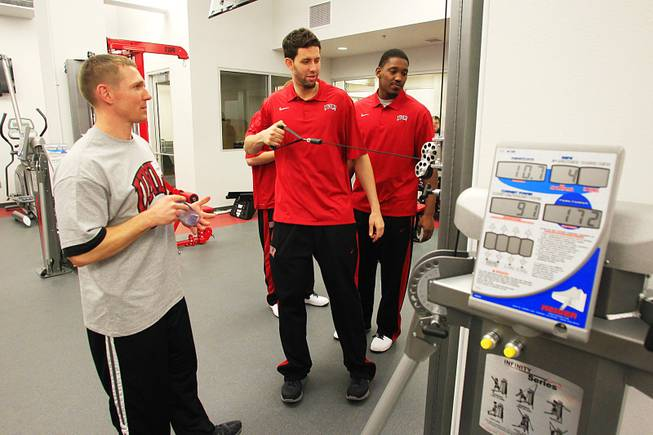 Strength and conditioning coach Jason Kabo watches as Carlos Lopez tries out a piece of equipment in the Joel Anthony weight room during the grand opening of UNLV's new basketball practice facility, the $11.7 million Mendenhall Center, Thursday, Jan. 19, 2012.