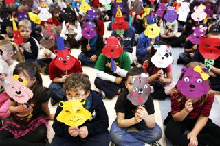 Students at Twitchell Elementary School display the bear masks they made after a workshop with Ron and Marsha Feller at their school in Henderson Friday, Ja. 20, 2012.