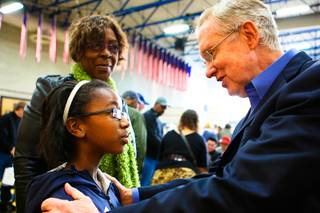 Sen. Harry Reid speaks with 10-year-old Aquilla El-Amin as her friend, Betty Carter, smiles beside her while attending the 2012 Democratic Caucus Saturday, Jan. 21, 2012, at Cheyenne High School.