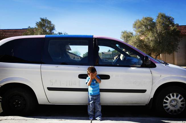 Aldo Ortega, 2, stands in front of the car donated to his family by the church of his mother, Belem Ortega, outside their home in Las Vegas on Jan. 24, 2012.