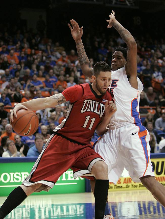 UNLV's Carlos Lopez (11) drives past Boise State's Kenny Buckner (42) during the first half of an NCAA college basketball game Wednesday, Jan. 25, 2012, in Boise, Idaho.   (AP Photo/Matt Cilley)